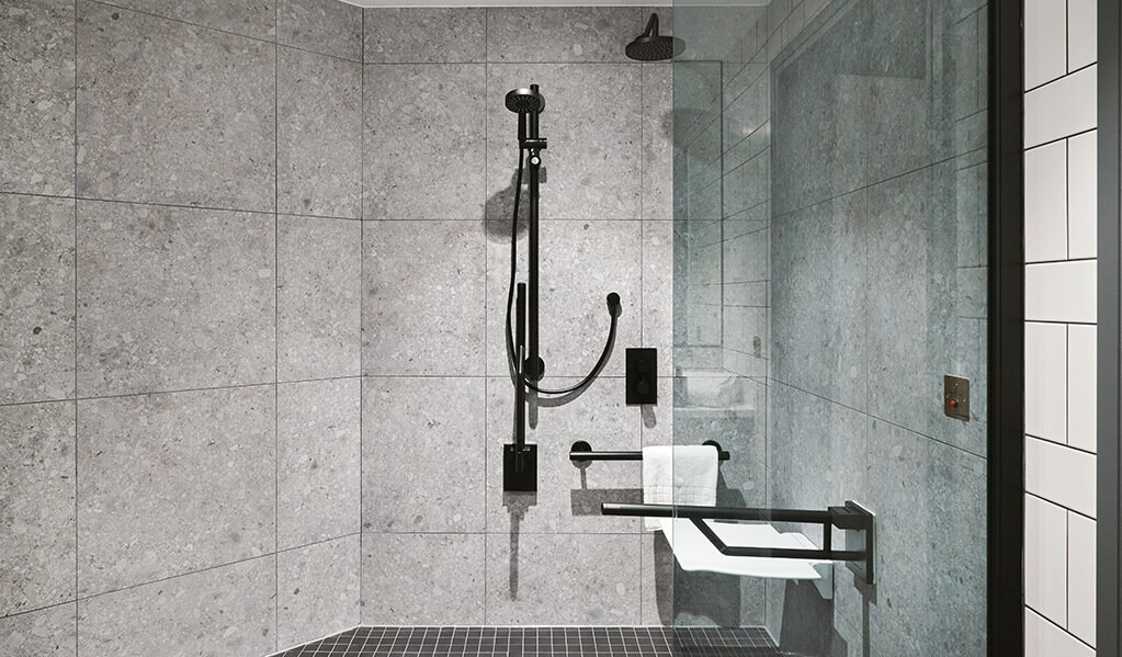 Hotel Brooklyn shower, large grey quartz tiles with matt black Doc M pack, shower seat and tinted shower glass screen.