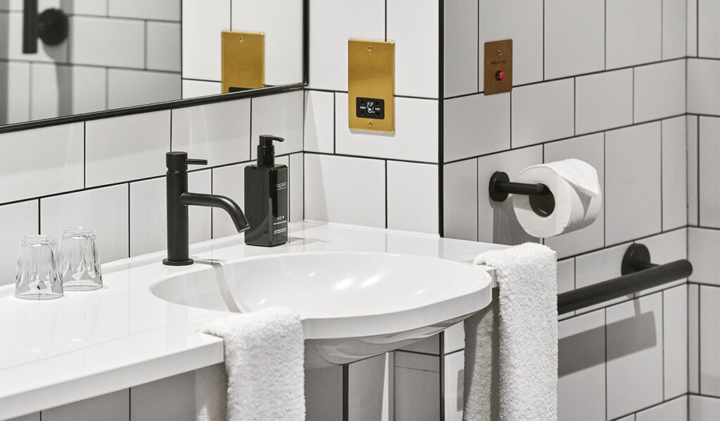 Hotel Brooklyn white tiled, black tile rim bathroom details, showcasing the integrated hand grab basin, matt black finishes along complimented with brass plated wall alarms.