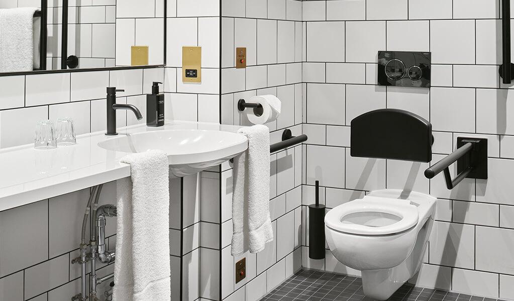 Hotel Brooklyn white tiled, black tile trim bathroom, showcasing the wall hung toilet with matt black back rest.