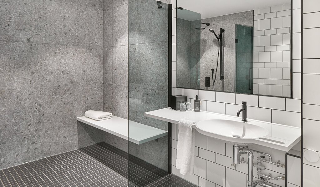 Hotel Brooklyn Bathroom, white wall tiles with black tile trims, showcasing a white sleek shower bench, wall to shower glass door.