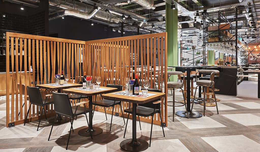 Hotel Brooklyn restaurant, exposed ceiling with lovely wooden statement fixed wall dividers, accents of sage green running through adding to the soft patterned flooring.