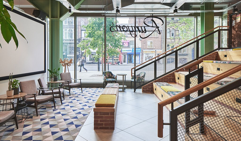 Hotel Brooklyn, beautifully wooden stairs which also act as quirky seating with lovely flowered pattern cushions. Large floor to ceiling windows adding a lot of natural lighting to the space with sage green accents running through with plantation.