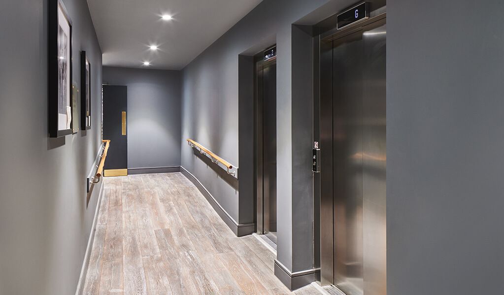 Hotel Brooklyn hallway, showcasing two chrome lifts with light wood hand rails running horizontally on each wall, complimented with spot lights above and wall art work.