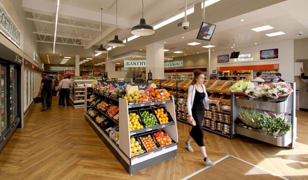 Interior of the Budgens store, displaying the light herringbone wood floor, colourful fruit and vegetables and bakery.