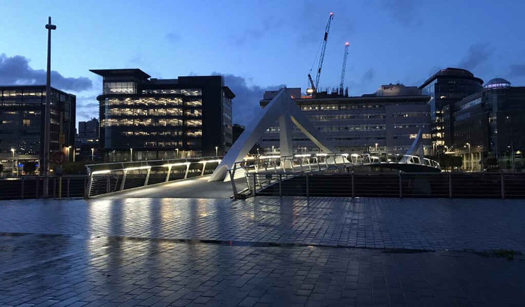 Barclays new Glasgow campus location at night time, lit up with lights showcasing the bridge over the river Clyde