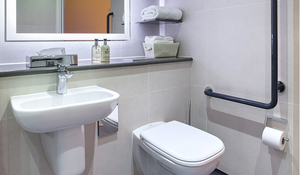 Bathroom with white wall hung toilet, L shaped hand rail and illuminated mirror above white hand basin with lovely chrome finishes.
