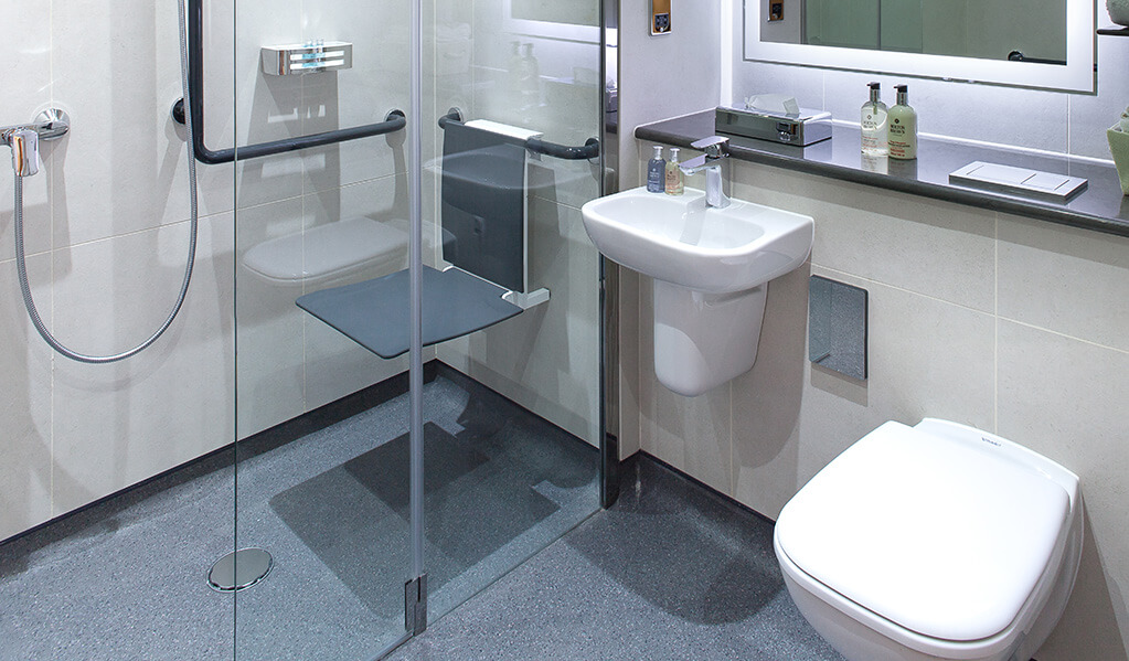Bathroom with wall hung white toilet, small white basin and a bifolding shower screen which homes a wall hung charcoal coloured shower seat and L shaped shower rail.