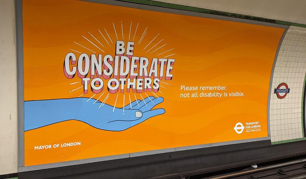 London Underground orange signage on wall reading 'Be considerate to others'.