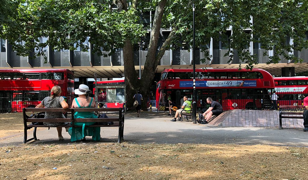 Exterior image of a red London double decker bus with people sat on benches admiring them.