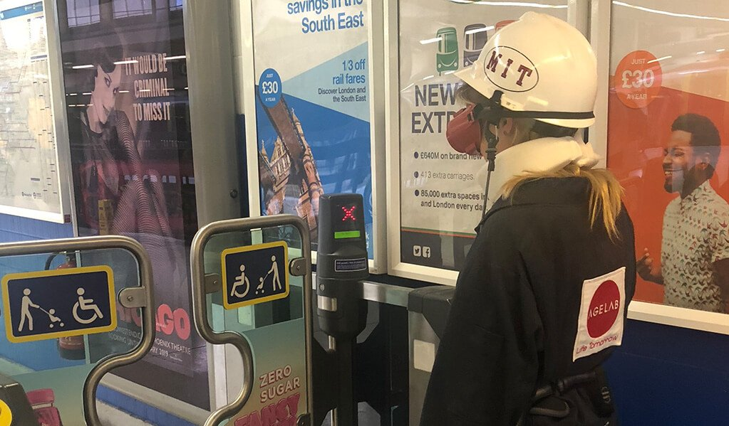 Person in an M.I.T age lab suit going through accessible ticket gates at train station