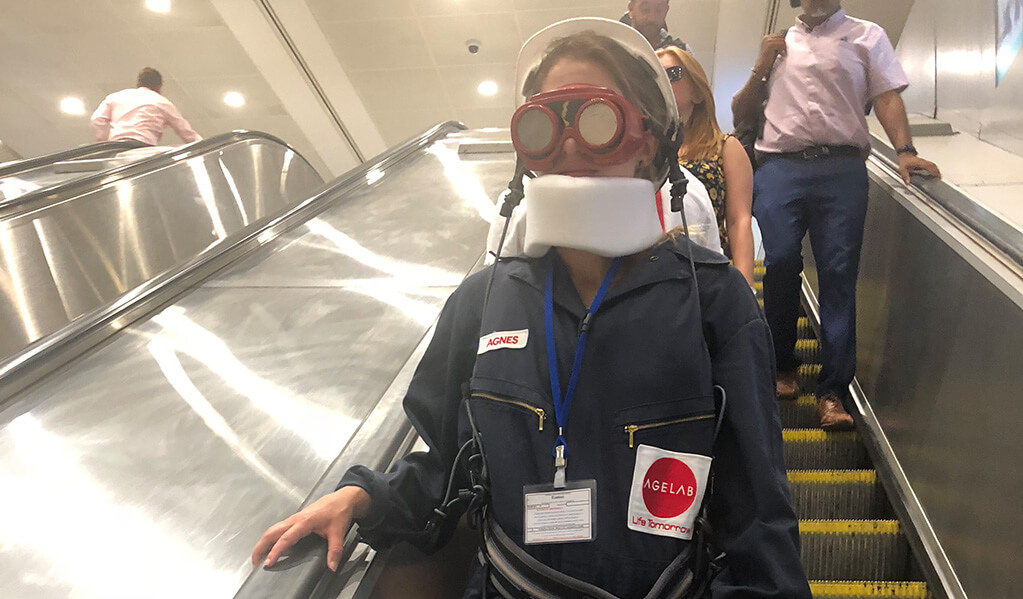 Person in a M.I.T age lab suit travelling down an underground escalator during a busy commute