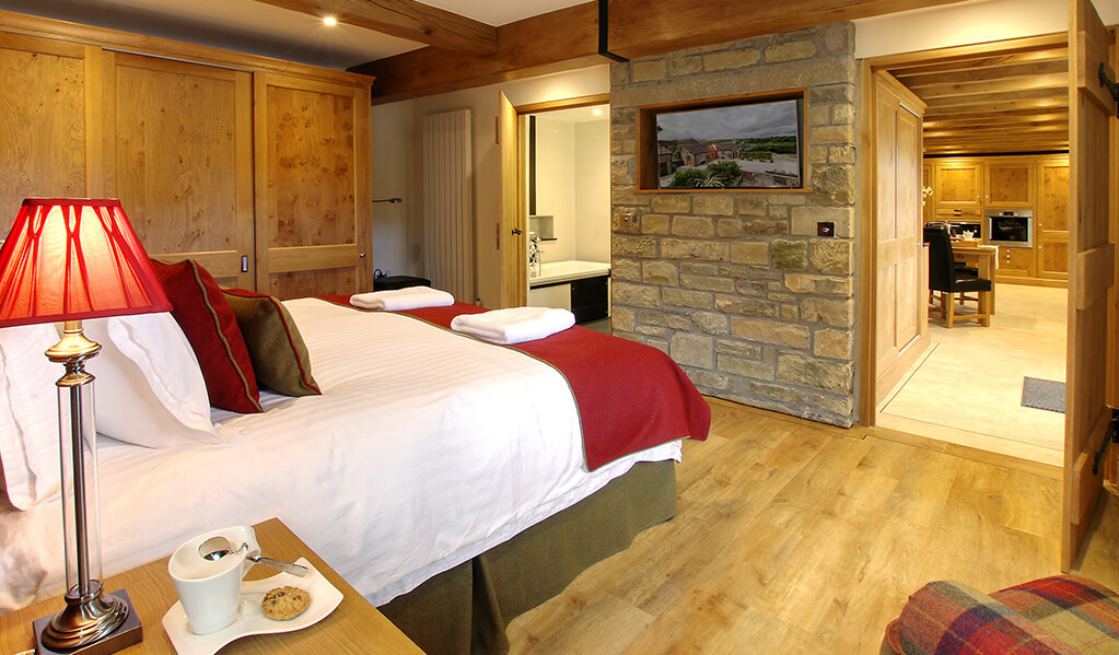 Light wood interior bedroom with exposed brick that holds an integrated television, double bed in the centre of the back wall with a view to the bathroom and kitchen.