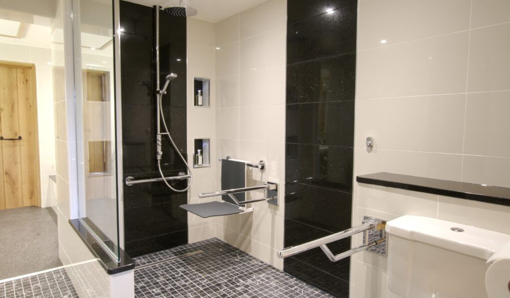 Monochrome interior tiled bathroom with view of chrome shower and charcoal grey seat down.
