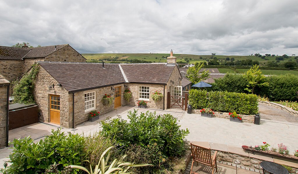 Exterior large angled view of the cottage in the Dales, L shaped building with large windows and light wood doors with a view of the garden which has lots of plants and tidy drive.