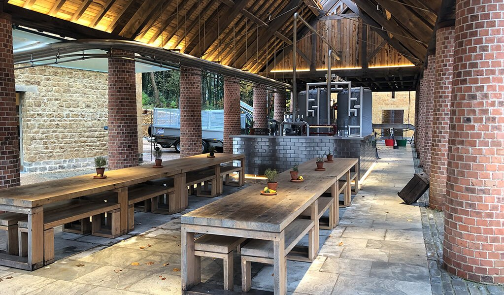 Open sided barn with brick columns and long wooden dining table down the central aisle