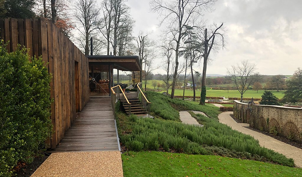Wooden exterior of a dining area over looking gardens with stairs and ramps built into greenery