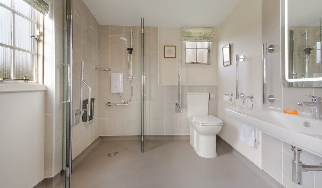 Neutral tone bathroom with chrome detailing throughout showcasing the bifold shower screen and chrome detailed shower.