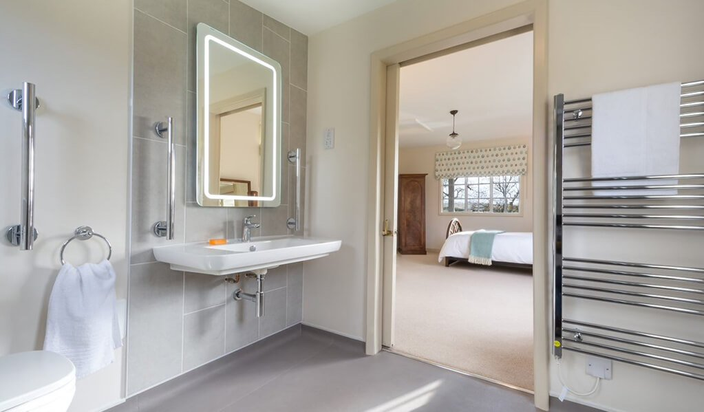 Neutral tone bathroom with chrome detailing throughout with illuminated mirror with view of cream coloured bedroom with lovely teal blue soft furnishings.