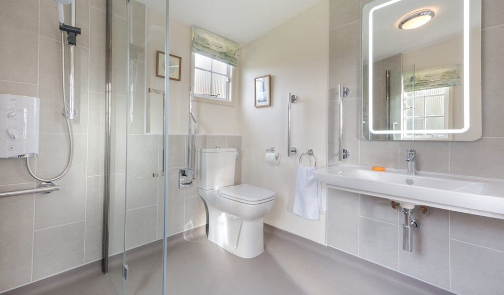 Neutral tone bathroom with chrome detailing throughout, illuminated rectangle mirror above large white basin.