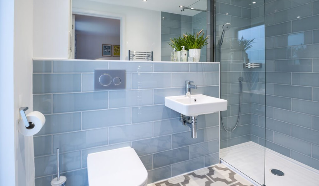 Details of large rectangle light blue wall tiles in bathroom with patterned grey and white flooring.