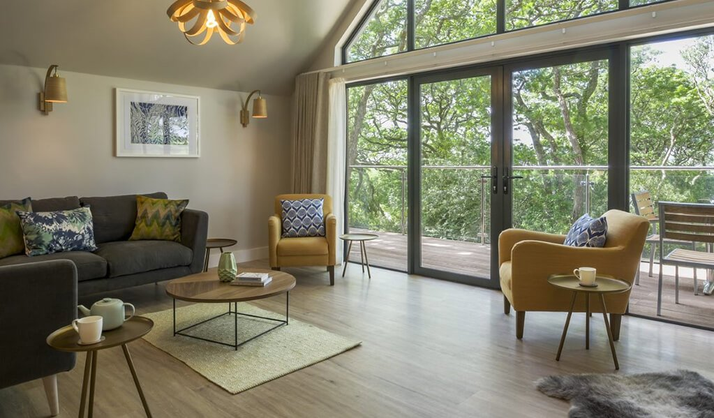 Open plan view of living area, mustard and grey coloured furnishings and brown wood flooring. Gorgeous floor to ceiling windows and double doors with view onto the balcony, surrounded by lovely bright green trees.