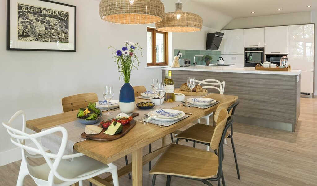 Statement 8 chair rectangle light wood dining room table, dressed with colourful food and cutlery with view of modern kitchen.