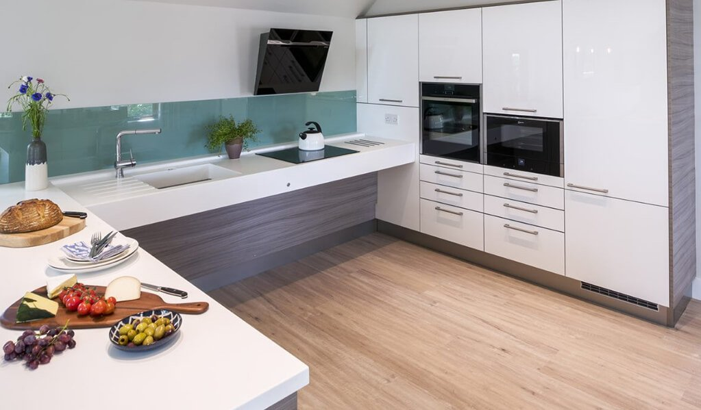 Grey wood and white U shaped smart modern kitchen with light wood flooring and chrome finishes.
