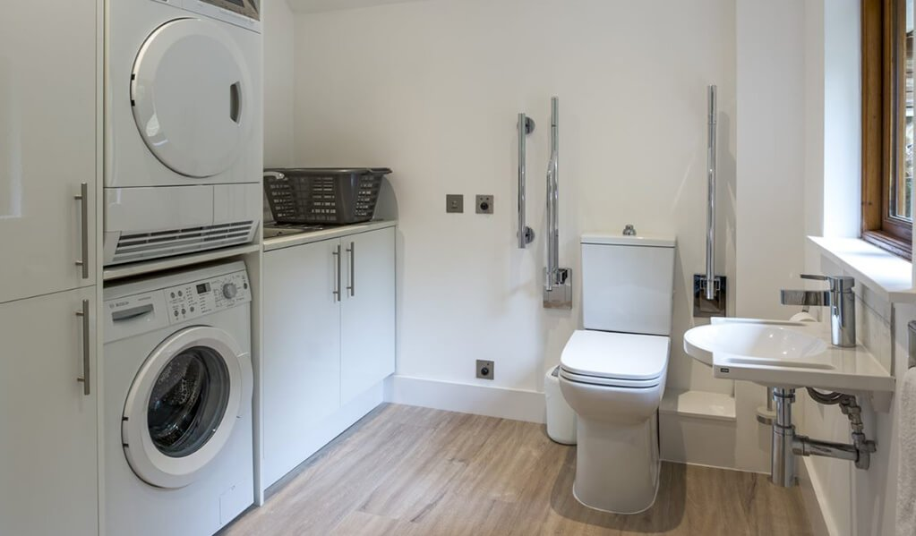 Utility room with white washing machine and dryer, an accessible modern toilet with chrome finished grabrails.