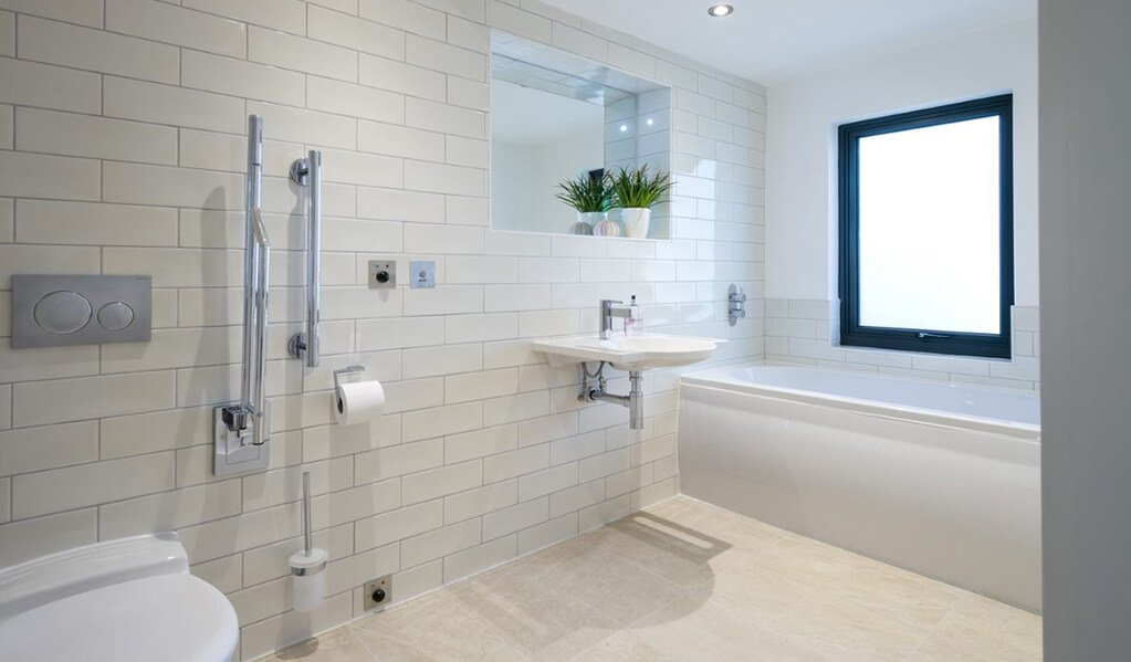 White modern tiled accessible bathroom with chrome finishes and a large white bath.