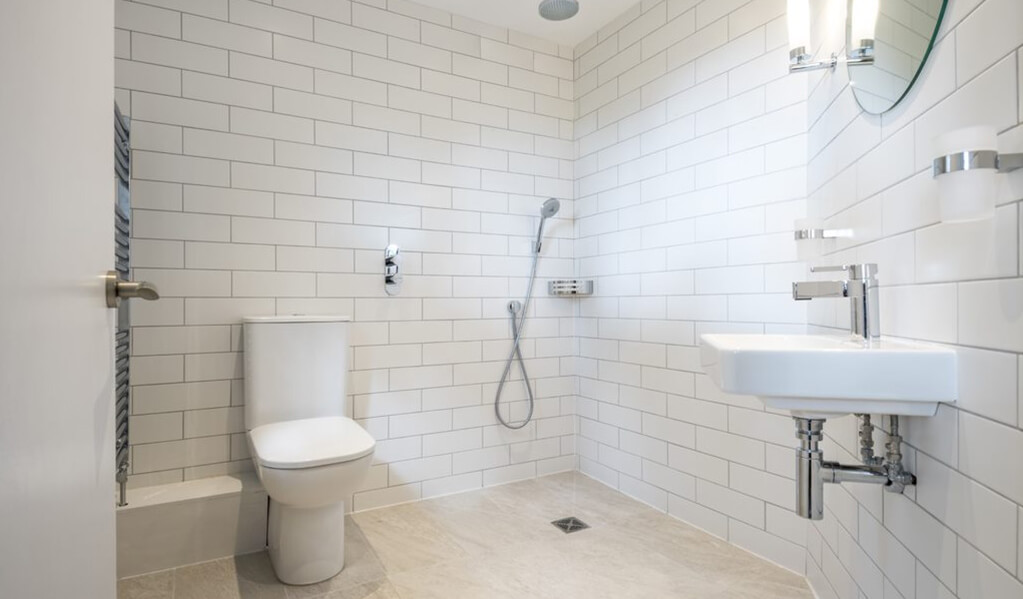 White modern tiled shower room with chrome finishes and standing toilet.