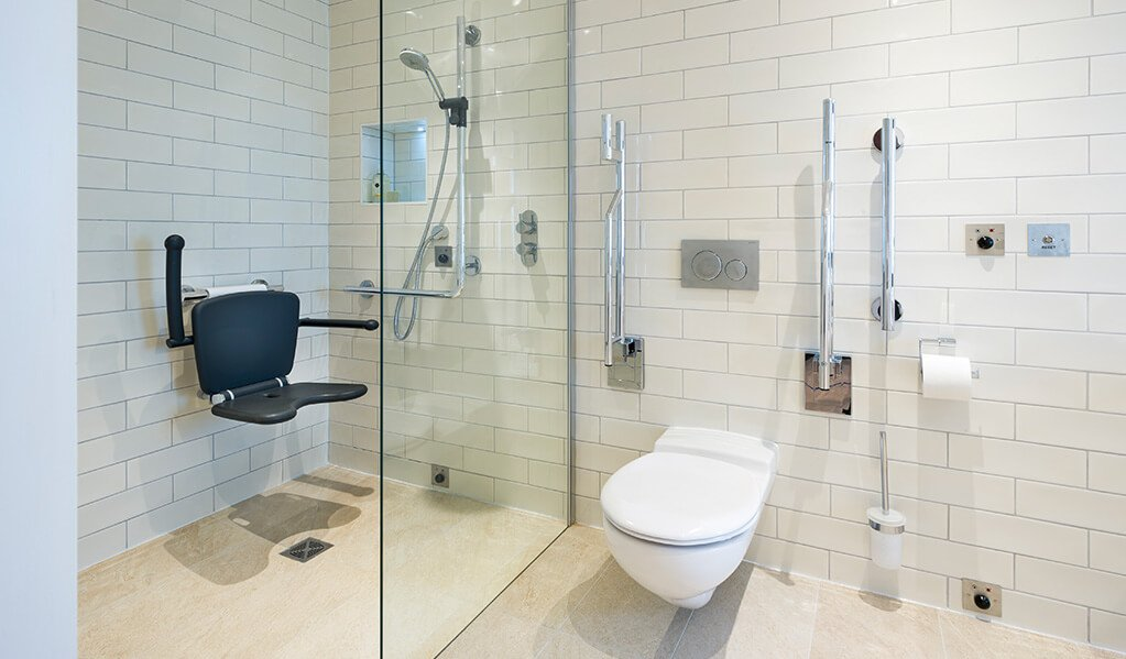 White modern tiled accessible bathroom with chrome finishes and large open shower with a matt black wall hung shower seat.