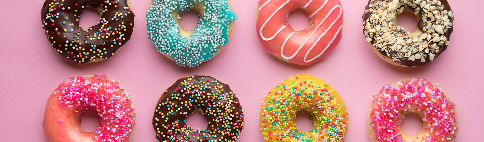 Variety of donuts on a pink background