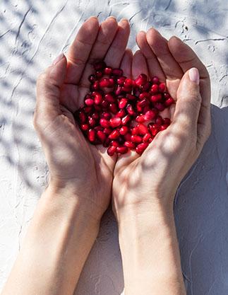 Hände auf weißem Untergrund mit roten Granatapfelkernen