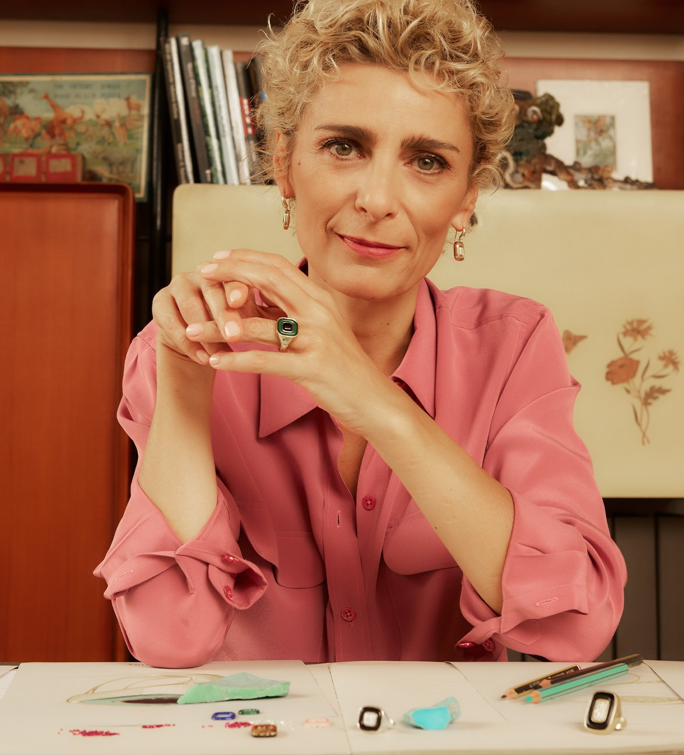 Portrait of Francesca Villa. She has short, curly blond hair and is wearing a pink collared shirt. On her desk are two of her ring peices.