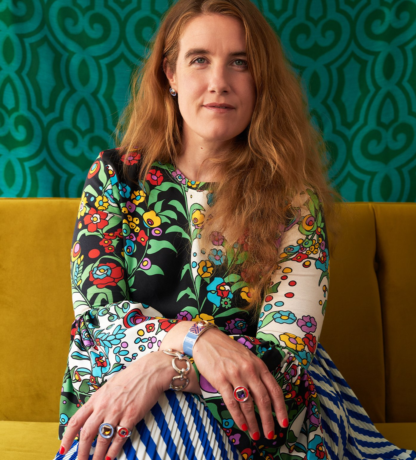 Portrait of Alice Cicolini. She has light eyes, fair skin, and long reddish hair. She is wearing a colorful dress with a 70s-era floral pattern, and is wearing several of her Mad Mod jewely peices.