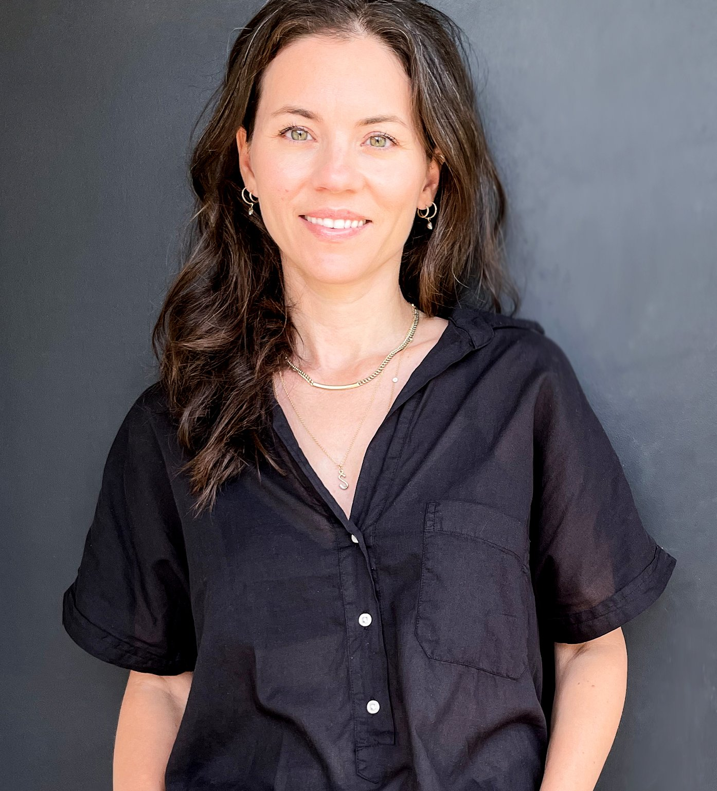 Portrait of Stacy Nolan. She has fair skin, light eyes, and nearly black hair. She is wearing a delicate chain necklace over a collared shirt with a deep neckline.