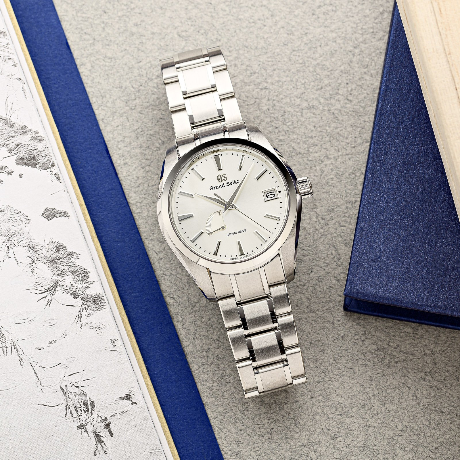 Light dial stainless steel Grand Seiko wristwatch on a bracelet.