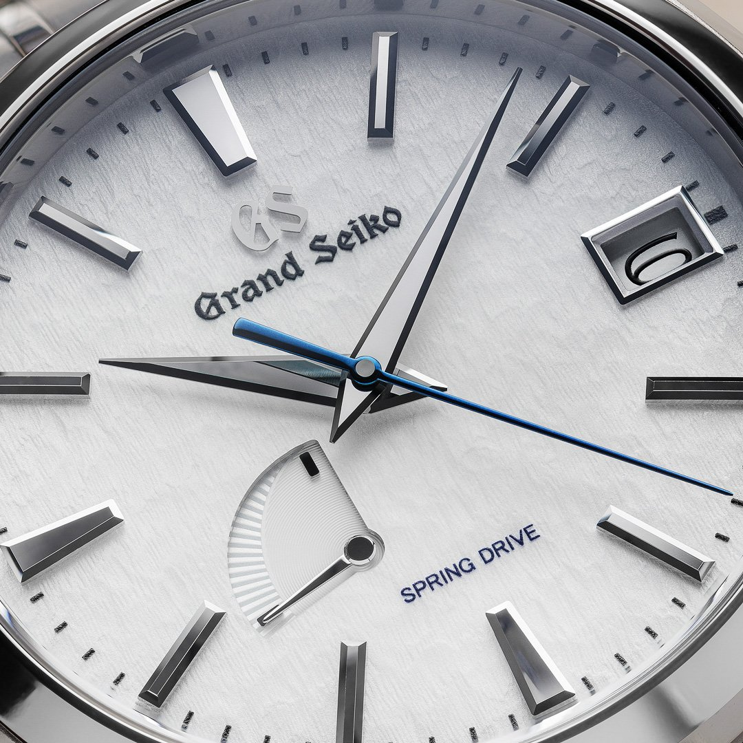 Grand Seiko SBGA211 - macro detail of the fine textured snowflake dial and blue accents.