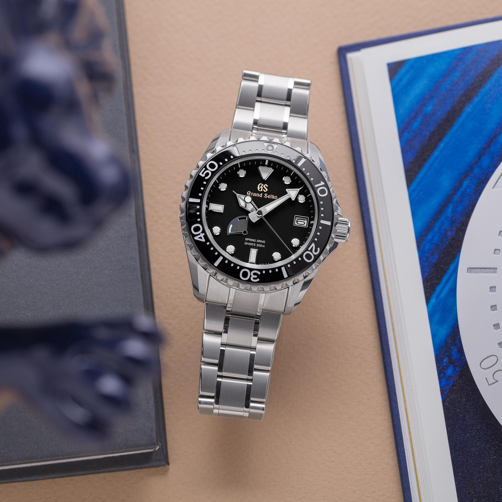 Grand Seiko SBGA231 wristwatch - a titanium cased, black dial diver atop a brown table.
