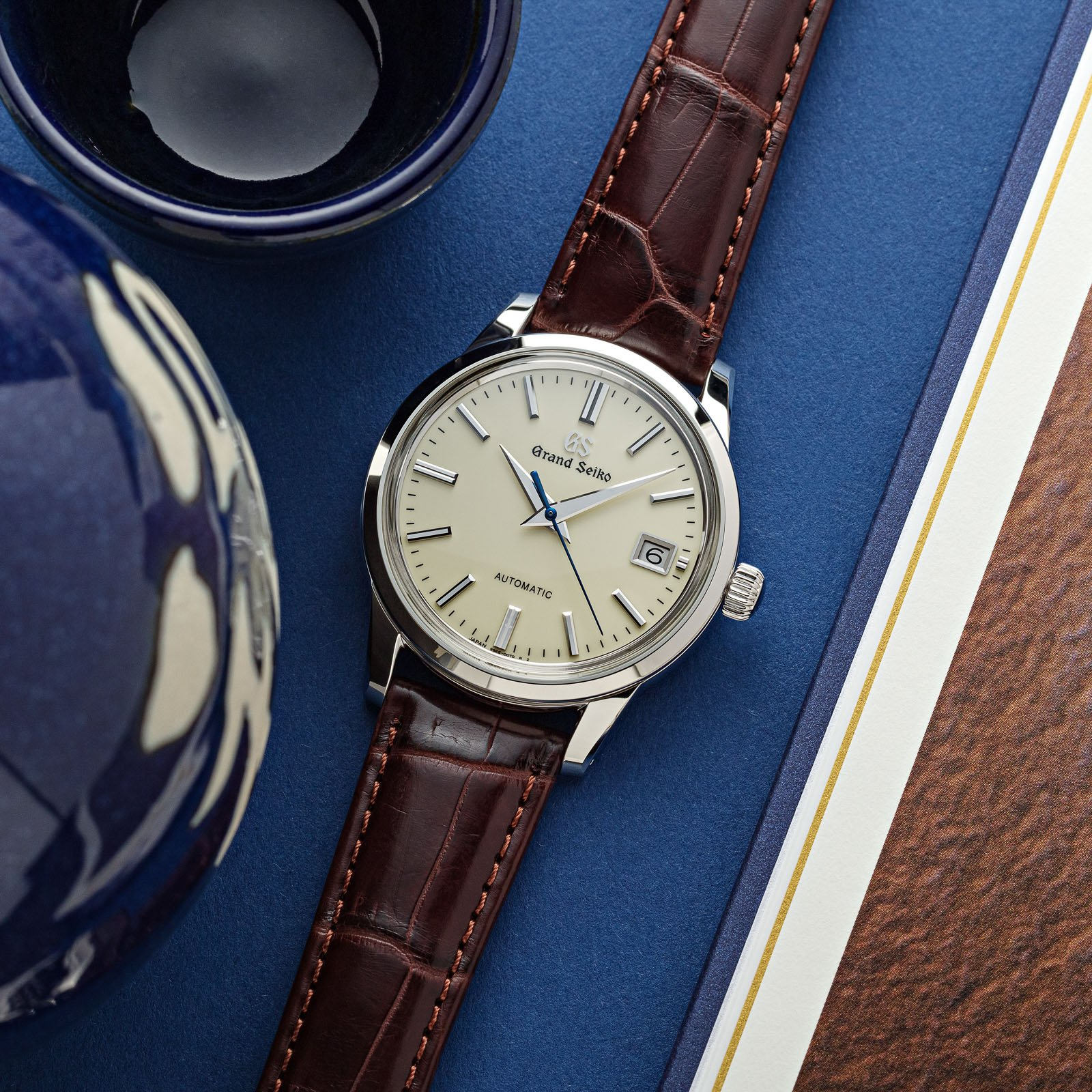 A classic ivory dial dress watch with a blue second hand on a brown strap.