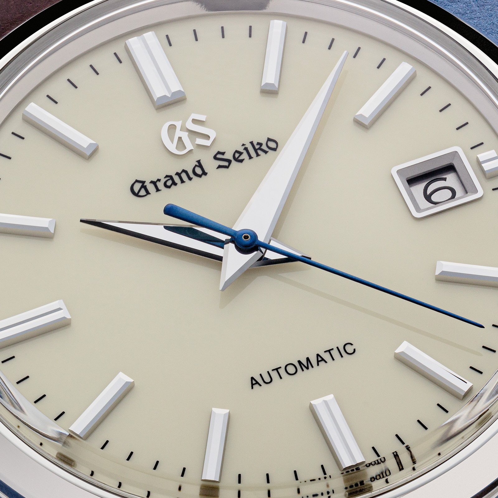 An ivory dial with silver tone markers and hands, and a blue second hand.