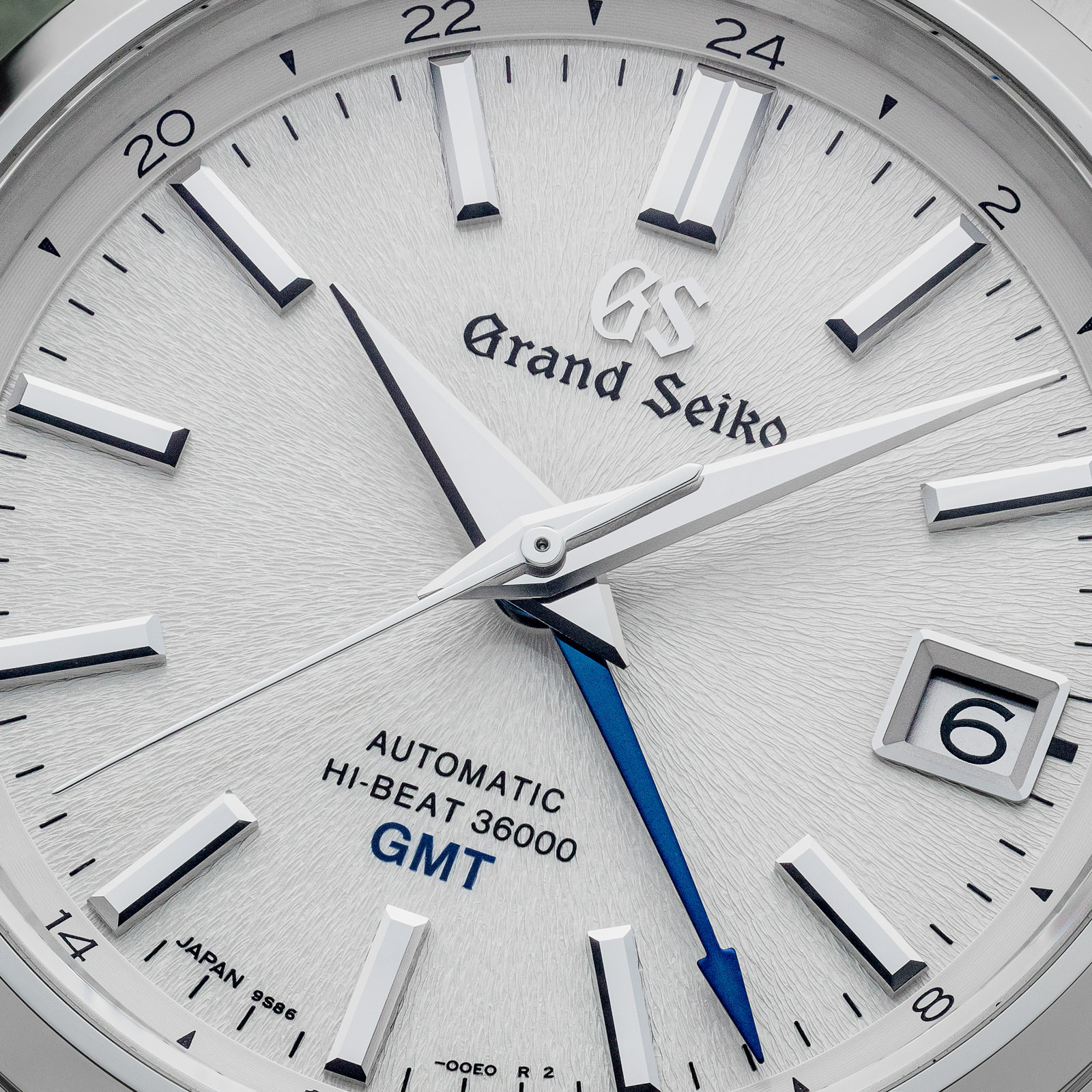 White textured dial wristwatch with a blue seconds hand.