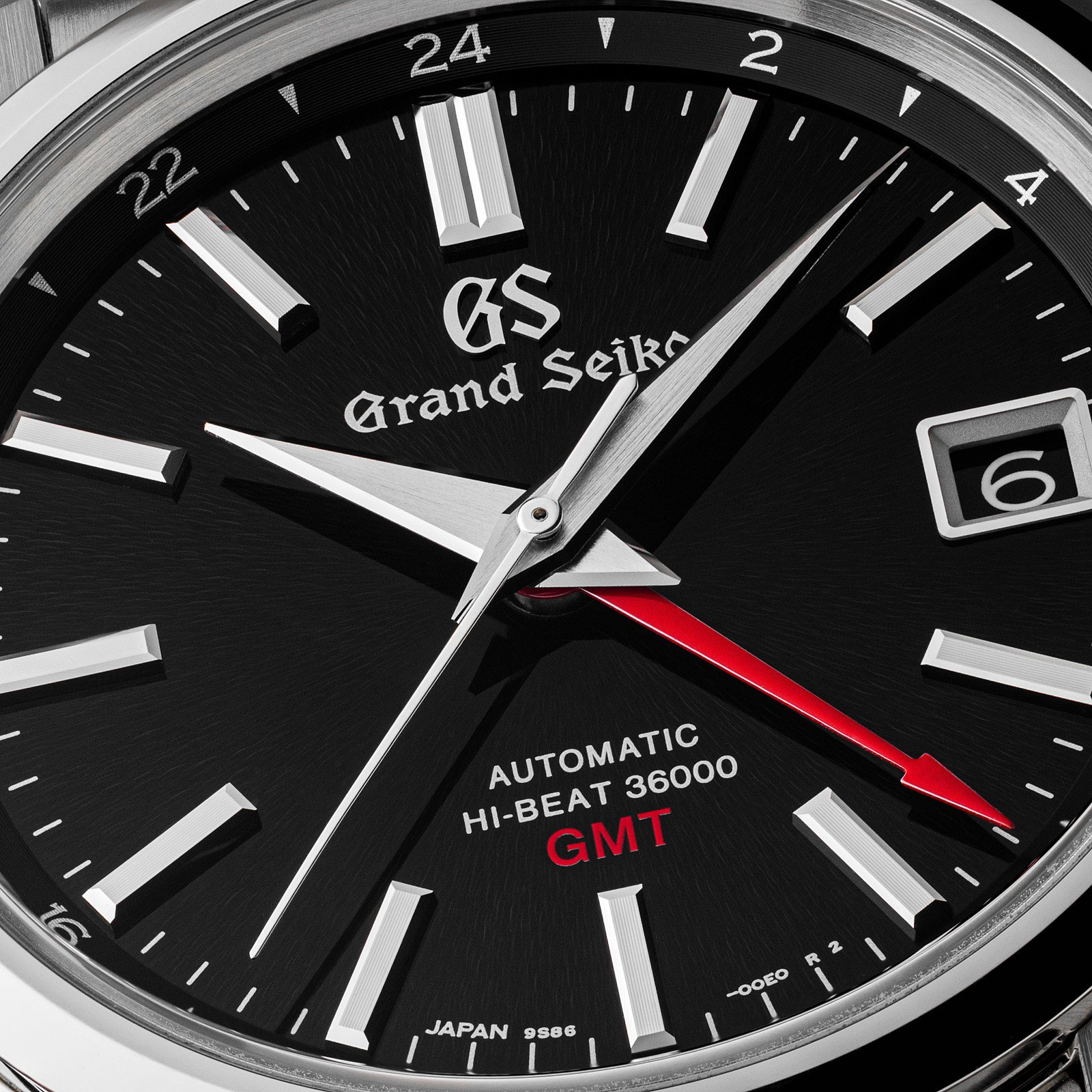 Closeup of black dial with red accents.