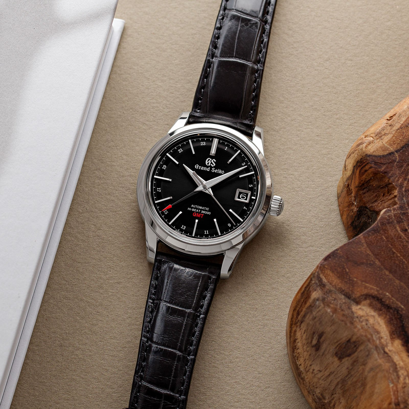 A dark dialed stainless steel Grand Seiko timepiece with a red-tipped GMT hand.