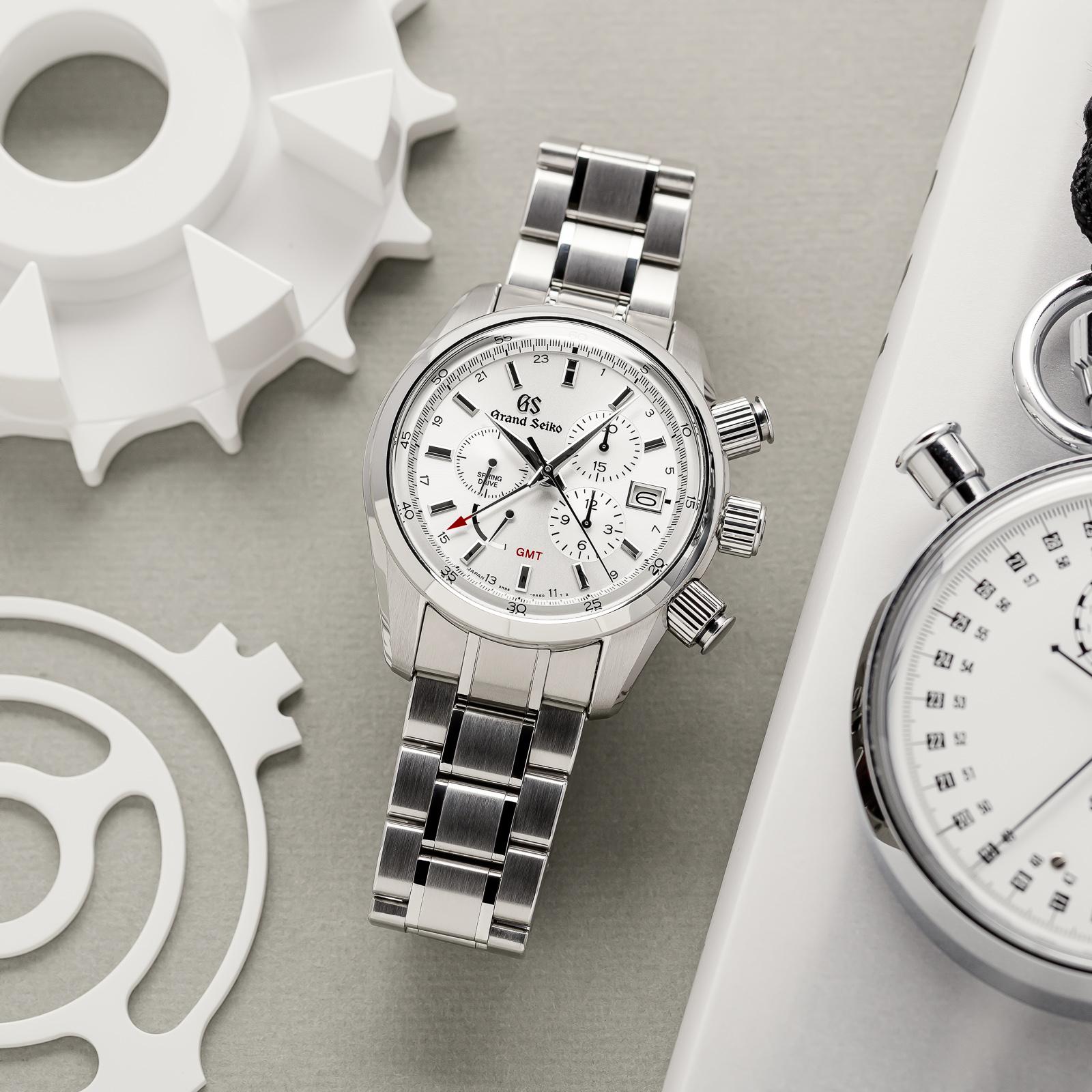 Grand Seiko chronograph SBGC201 - white dial, stainless steel wristwatch atop a gray table.
