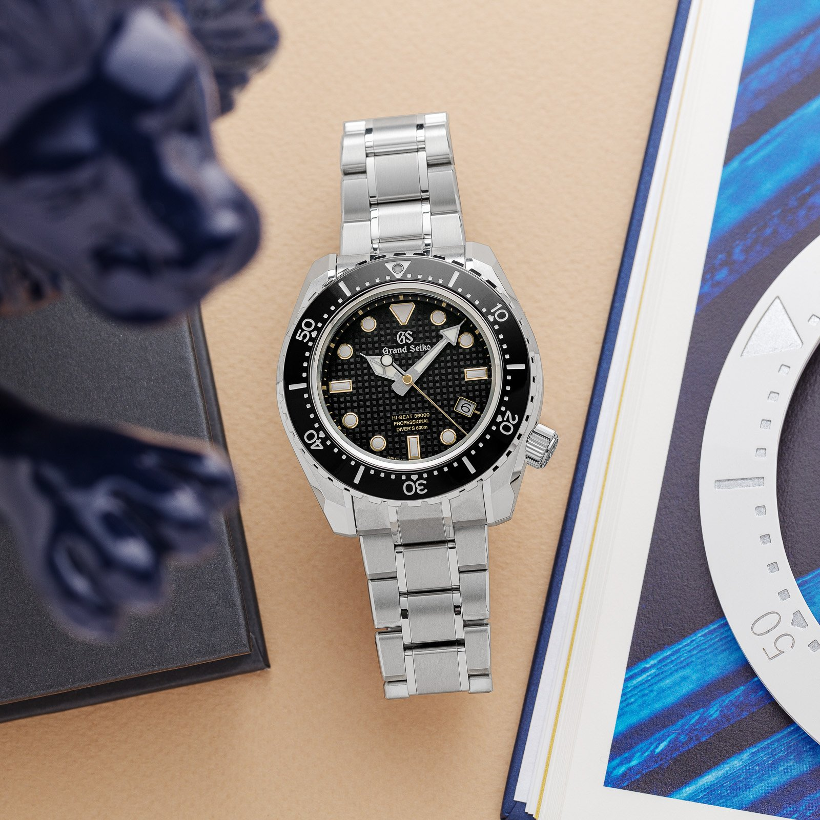 Grand Seiko SBGH255 - a black-dialed diver's wristwatch with a titanium case and bracelet atop a table.