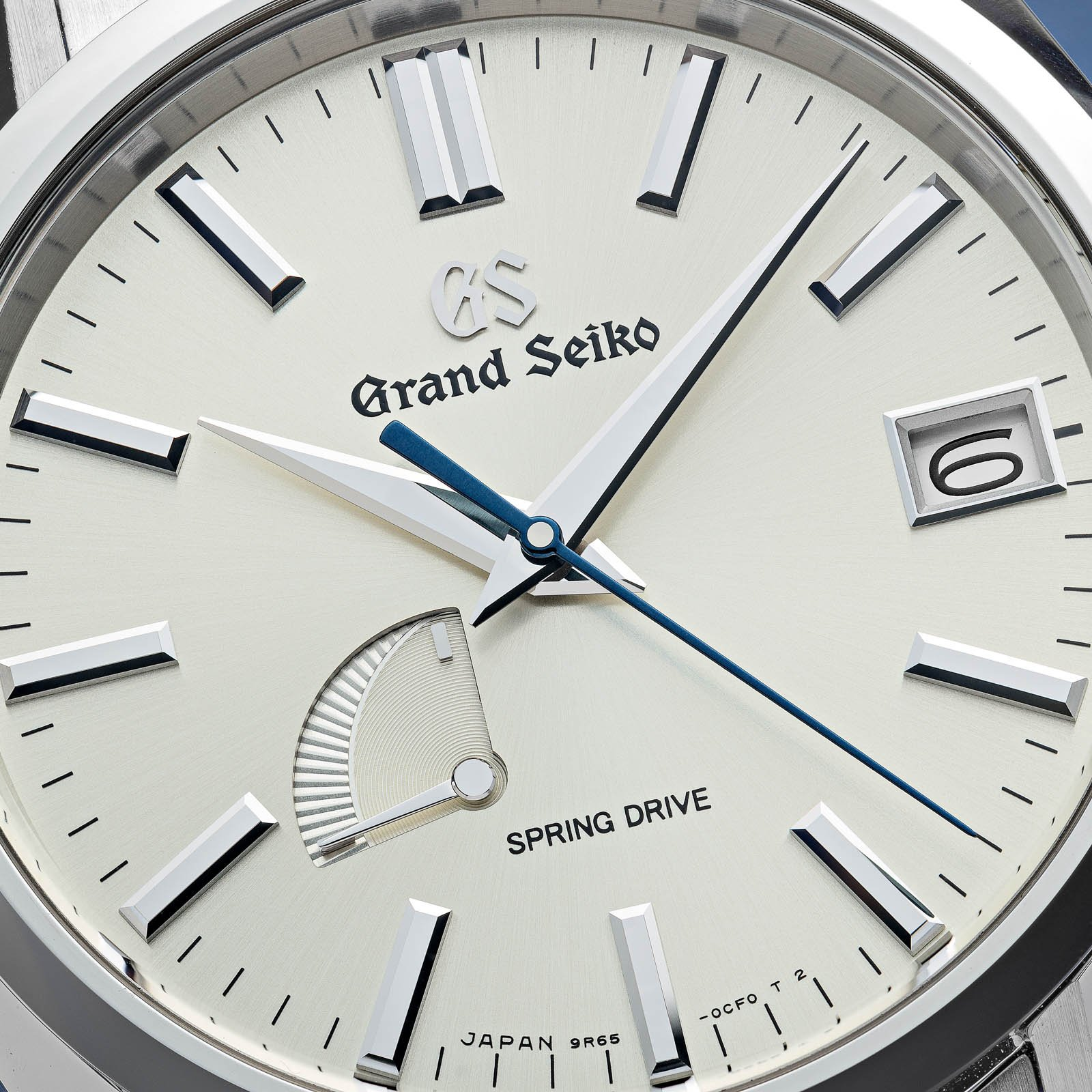 A watch with a champagne dial with silver tone indexes, hands, and a blue second hand.