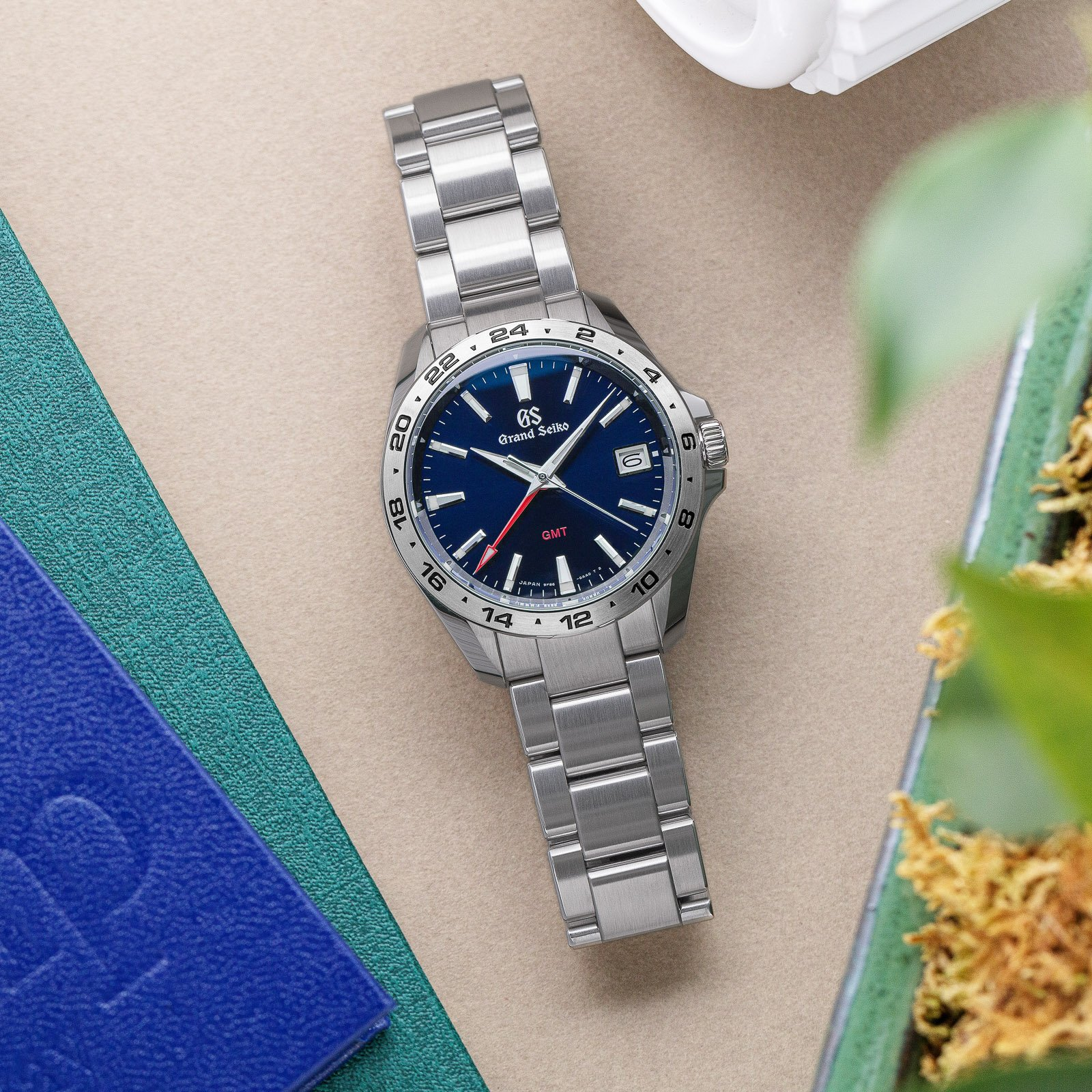 Grand Seiko SBGN005 - blue dial stainless steel wristwatch atop a table.