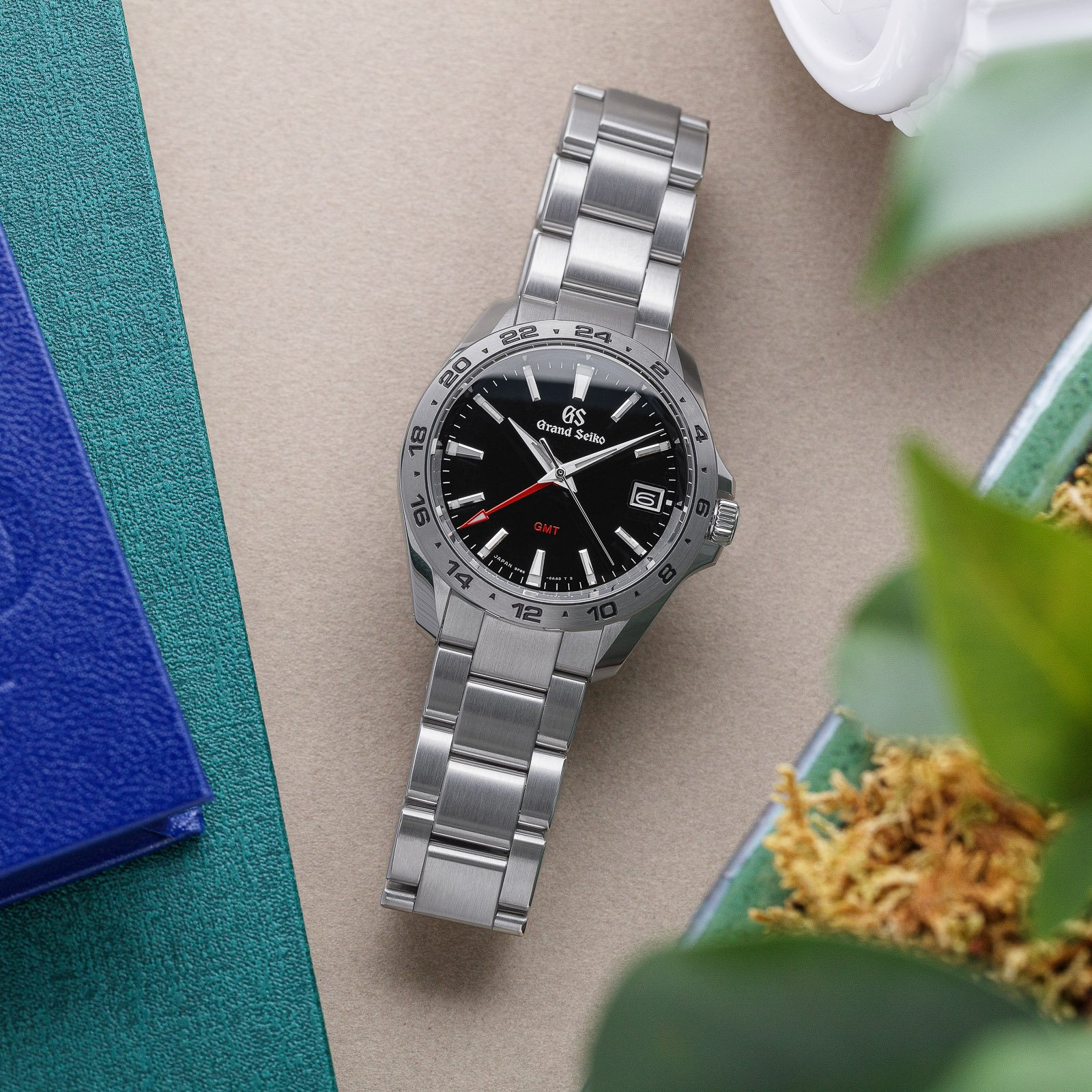 Grand Seiko SBGN003 - black dial stainless steel wristwatch atop a table.