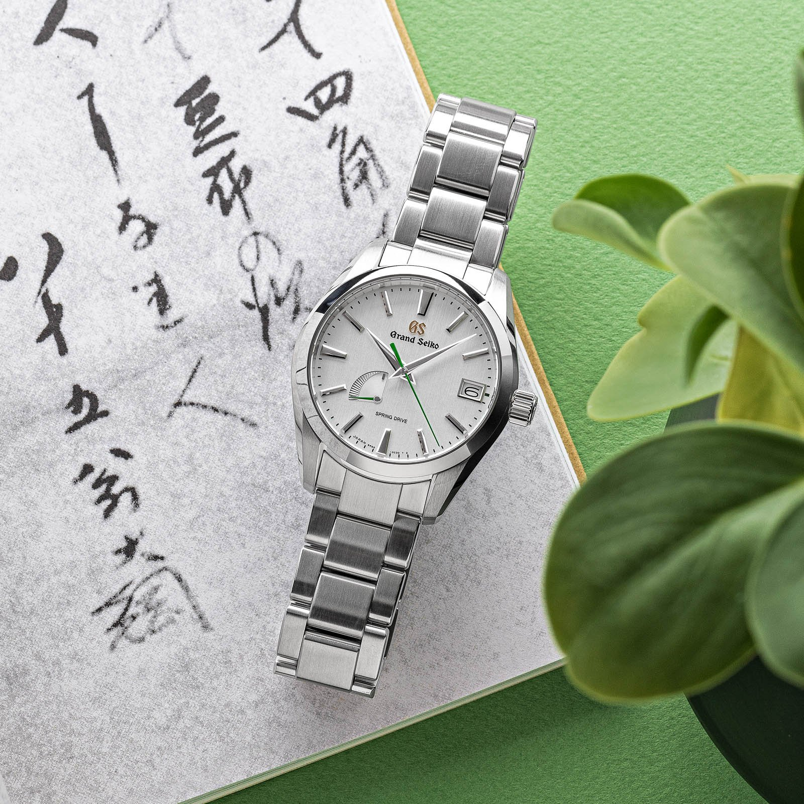 A light dial stainless steel wristwatch with a matching bracelet and green second hand.